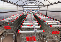 Tienda roja vacía grande de Auchan del carro de la compra Imagenes de archivo