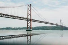 Tienda un puente sobre el 25 de abril llamado en Lisboa en Portugal con la reflexión en agua Imagen de archivo libre de regalías