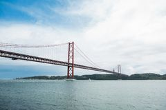 Tienda un puente sobre el 25 de abril llamado en Lisboa en Portugal contra el cielo Foto de archivo libre de regalías