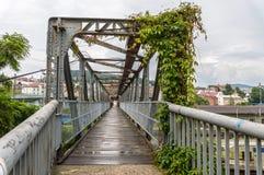 Tienda un puente sobre el paso sobre una ciudad con las enredaderas sobre ella Fotos de archivo