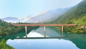 Tienda un puente sobre el reflejo en un Green River, colinas verdes y montañas en el bacground Imagen de archivo