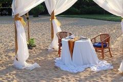 Tienda y una tabla para una cena romántica en la playa Fotografía de archivo