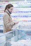 Tiendas de comestibles de compra bastante youman en un supermercado Imágenes de archivo libres de regalías