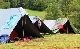 Tiendas en un campo del explorador y un lavadero de sequía hacia fuera a secarse Fotografía de archivo