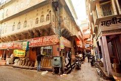 Tiendas privadas con la comida y las especias en la calle estrecha de la ciudad india histórica Imagen de archivo libre de regalías