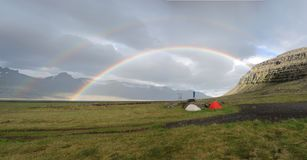 Protected tents. Campsite in Iceland under a double giant rainbow Royalty Free Stock Photography
