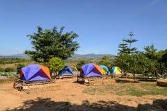 Tiendas turísticas que acampan entre prado en la montaña Fotografía de archivo libre de regalías