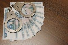 Tienduizendtal Russische roebels waarop politiehandcuffs op een noot-gekleurde lijst liggen Schending van de wet, corruptie, fina royalty-vrije stock afbeeldingen