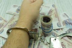 Tienduizendtal Russische roebels waarop politiehandcuffs op een noot-gekleurde lijst liggen Schending van de wet, corruptie, fina royalty-vrije stock foto's