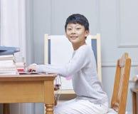 Tiener Aziatische jongen die, camera bekijken & het net surfen glimlachen Royalty-vrije Stock Afbeelding