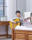 Tiener Aziatische jongen die & het praktizeren gitaar thuis leren Royalty-vrije Stock Fotografie