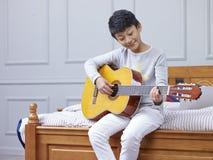 Tiener Aziatische jongen die & het praktizeren gitaar thuis leren Stock Foto's