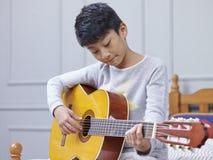 Tiener Aziatische jongen die & het praktizeren gitaar thuis leren Royalty-vrije Stock Afbeeldingen