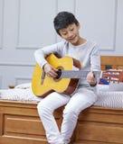 Tiener Aziatische jongen die & het praktizeren gitaar thuis leren Royalty-vrije Stock Foto