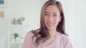 Tiener Aziatische vrouw die het gelukkige glimlachen voelen en aan camera kijken terwijl thuis in haar slaapkamer ontspan stock videobeelden