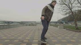 Tiener berijdend skateboard onderaan stoep in stad stock video