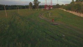 Tiener berijdende fiets in het land, luchtmening stock videobeelden