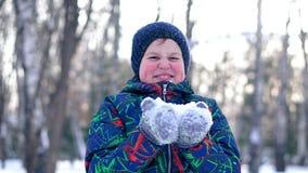 Tiener blazende sneeuw van zijn handen stock footage