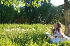 Tiener blazende zaden van een paardebloembloem in een de lentepark Royalty-vrije Stock Foto's