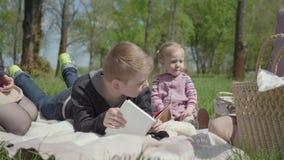 Tiener blonde jongen die op de deken in het park liggen die het boek, leuk meisje in een roze kledingszitting dichtbij lezen Twee stock video