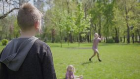 Tiener blonde jongen het spelen frisbee in het park met zijn moeder Het kind die het stuk speelgoed maar vrouw werpen vangt het n stock video
