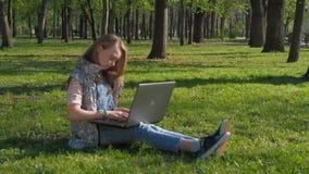 Tiener die aan laptop in aard werken Het meisje zit op het gras in het park Op een zonnige dag in de verse lucht met laptop stock videobeelden
