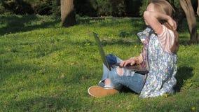 Tiener die aan laptop in aard werken Het meisje zit op het gras in het park Op een zonnige dag in de verse lucht met laptop stock video