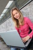Tiener die aan laptop werkt stock fotografie