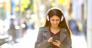 Tiener die aan muziek luisteren die in de straat lopen stock footage