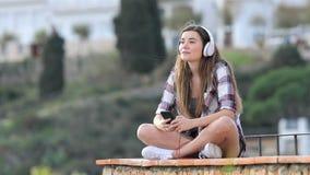 Tiener die aan muziek luisteren en op een richel ademen stock video