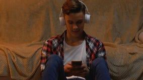 Tiener die aan muziek luisteren en smartphone gebruiken, die overzicht van nieuw album verlaten stock video