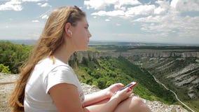 Tiener die aan muziek met hoofdtelefoons op smartphone op een achtergrond van bergen luisteren stock videobeelden