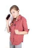 Tiener die aan Muziek op Haar Cellphone luisteren die die en bij Camera dansen glimlachen op Wit wordt geïsoleerd Royalty-vrije Stock Foto's