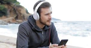 Tiener die aan muziek op het strand het letten op overzees luisteren stock video
