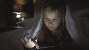 Tiener die in bed een tablet in sociaal Internet in het donkere licht spelen Sluit omhoog van meisje het letten op video op stock footage
