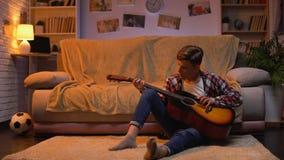 Tiener die bestudeert gitaar te spelen die over de hobby van de musicuscarrière, levensstijl droomt stock footage