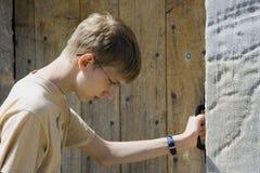 Tiener die bij een oude deur klopt Stock Foto's