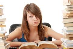 Tiener die bij het bureau bestudeert dat wordt vermoeid stock afbeelding