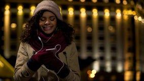 Tiener die in boodschapper app babbelen en aan muziek op haar smartphone luisteren stock afbeelding