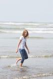 Tiener die in de oceaan lopen stock afbeelding