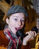 Tiener die door oude uitstekende telefoon spreken royalty-vrije stock afbeelding