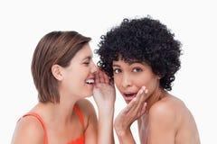 Tiener die een geheim fluistert aan een vriend stock afbeelding