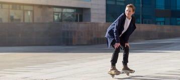 Tiener die een scateboard berijden op de promenade met exemplaarruimte stock afbeeldingen