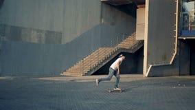 Tiener die een skateboard in een stad, stedelijke achtergrond, langzame motie berijdt stock videobeelden
