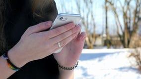 Tiener die een zilveren slimme telefoon in openlucht houden stock video