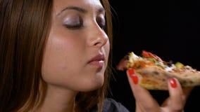 Tiener die en plak van ongezonde pizza met vlees en groenten bijten eten stock videobeelden
