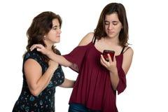 Tiener die haar moeder verhinderen haar telefoon te zien stock afbeelding