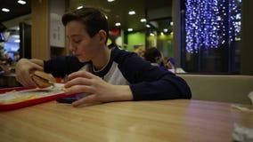 Tiener die Hamburger en spel in Smartphone eten stock footage
