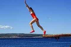 Tiener die in het overzees op de zon springen royalty-vrije stock foto's