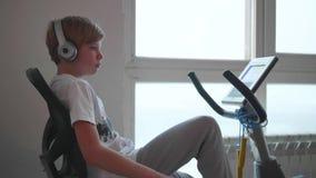 Tiener die in hoofdtelefoons aan muziek op een stationaire Fietsuitoefenaars luisteren Gymnastiek en gezonde levensstijl stock video